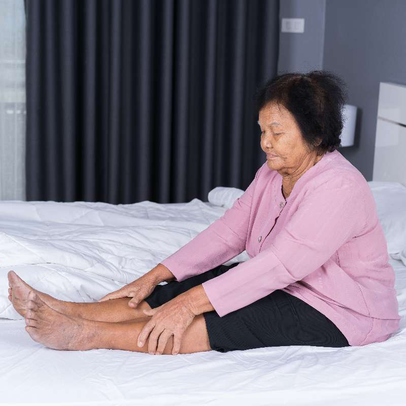 Elderly woman sitting upright in bed with legs straight