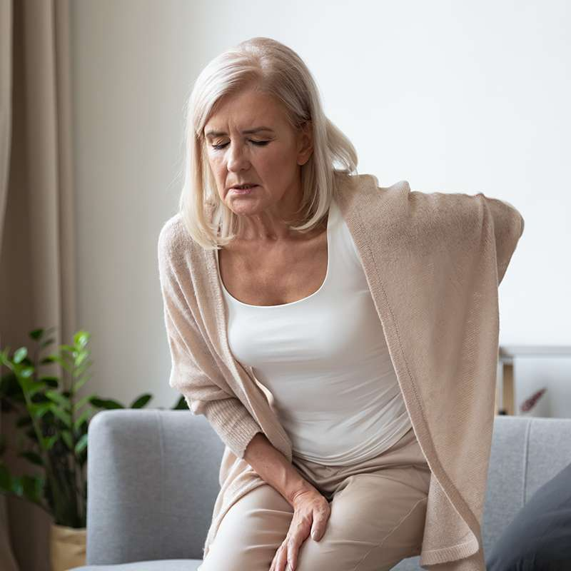 Women with osteoarthritis in her back feeling pain from cold weather