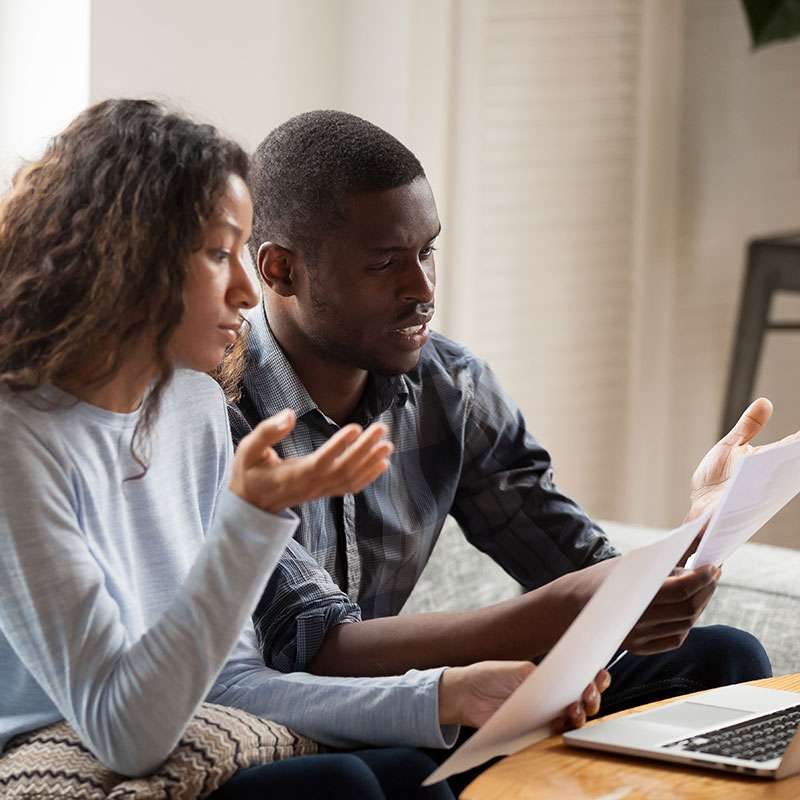 African American couple reviews health insurance documents
